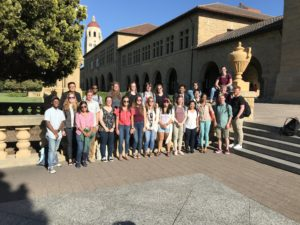 A group of students poses in front of a building on the Stanford campus
