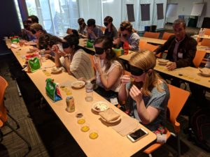 Students sitting at tables blindfolded and tasting olive oil