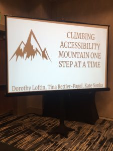 "Slide projector showing a slide that reads ""Climbing Accessibility Mountain One Step at a Time. Dorothy Loftin, Tina Rettler-Pagel, Kate Sonka."""